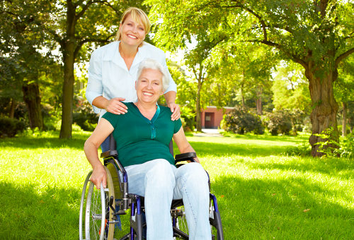 patient sitting on a wheelchair with her caregiver