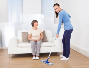 lady cleaning the floor and old woman sitting on a couch
