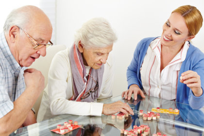 caregiver and seniors playing board games